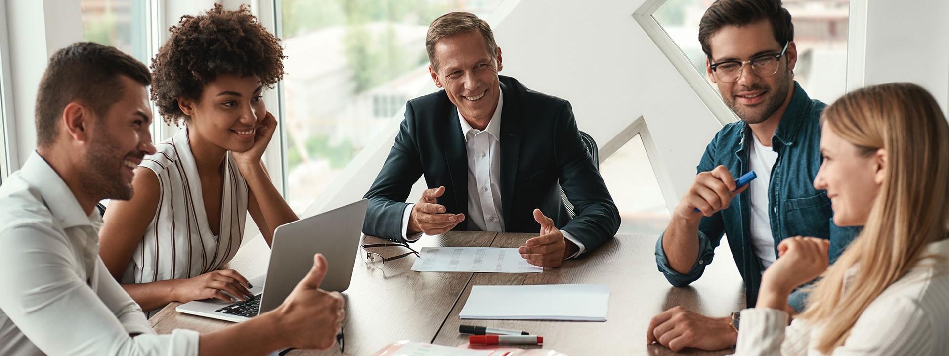 Eine Gruppe 30 bis 50-jähriger Männer und Frauen sitzen im Büro an einem Tisch und diskutieren.