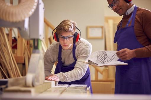 Ein etwa 16 jähriger Junge steht an einer Werkbank und schneiden ein Stück Holz an der Kreissäge zu. Neben ihm steht der Werkstattmeister und leitet ihn an.