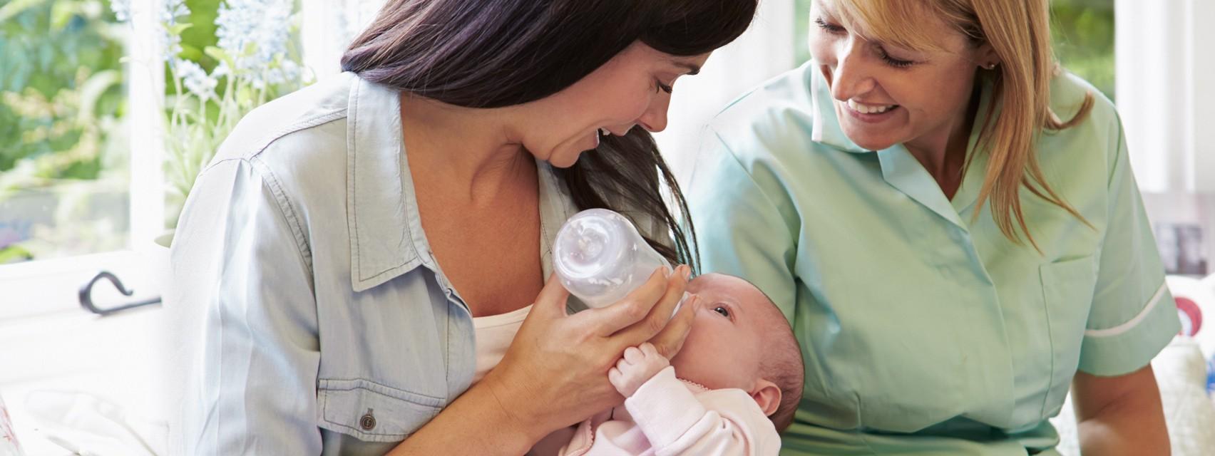 Zwei Frauen füttern ein Baby mit einer Flasche.