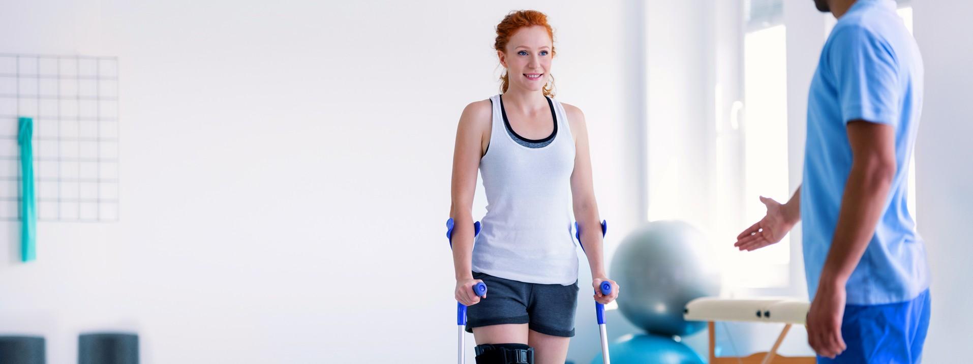 rothaarige sportliche  junge Frau mit Krücken und Knieverletzung bei der stationären Reha