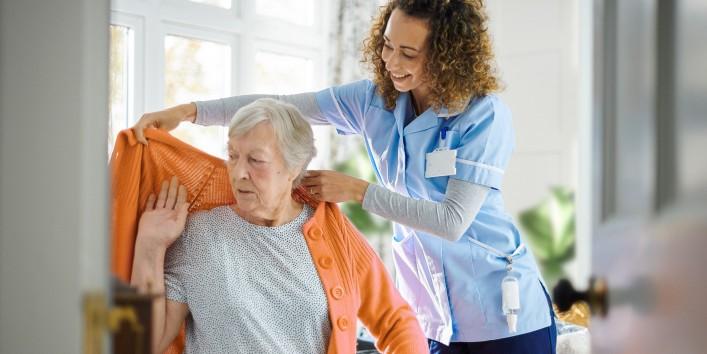 Alter Frau wird von Krankenpflegerin in die Jacke geholfen