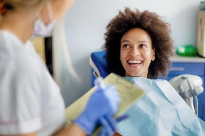 Lächelnde Frau in Zahnarztpraxis blickt zum Zahnarzt.