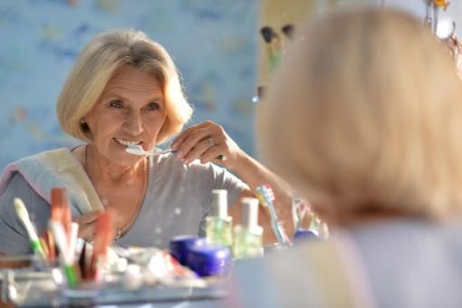 Eine etwa 60 jährige Frau steht vor dem Spiegel und putzt sich die Zähne.