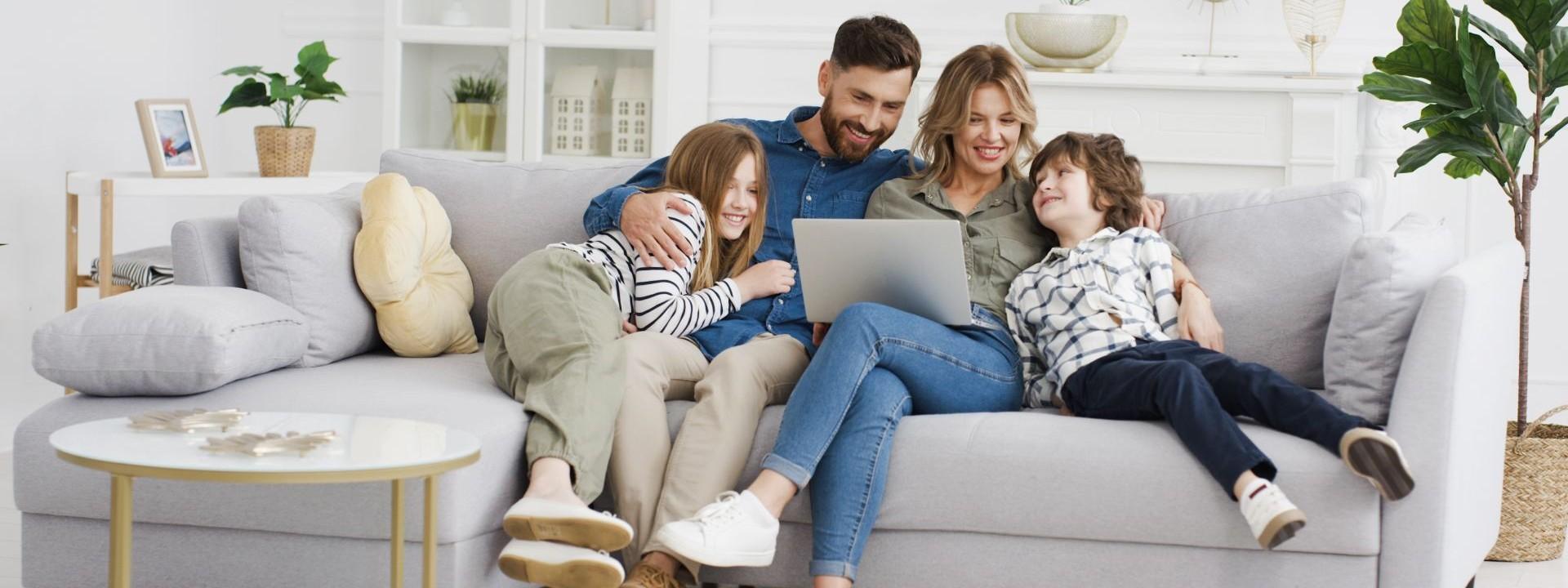Eine Familie mit zwei Kindern sitzen gemeinsam auf einem Sofa im Wohnzimmer. Alle schauen gemeinsam auf einen Laptop und lachen ausgiebig.
