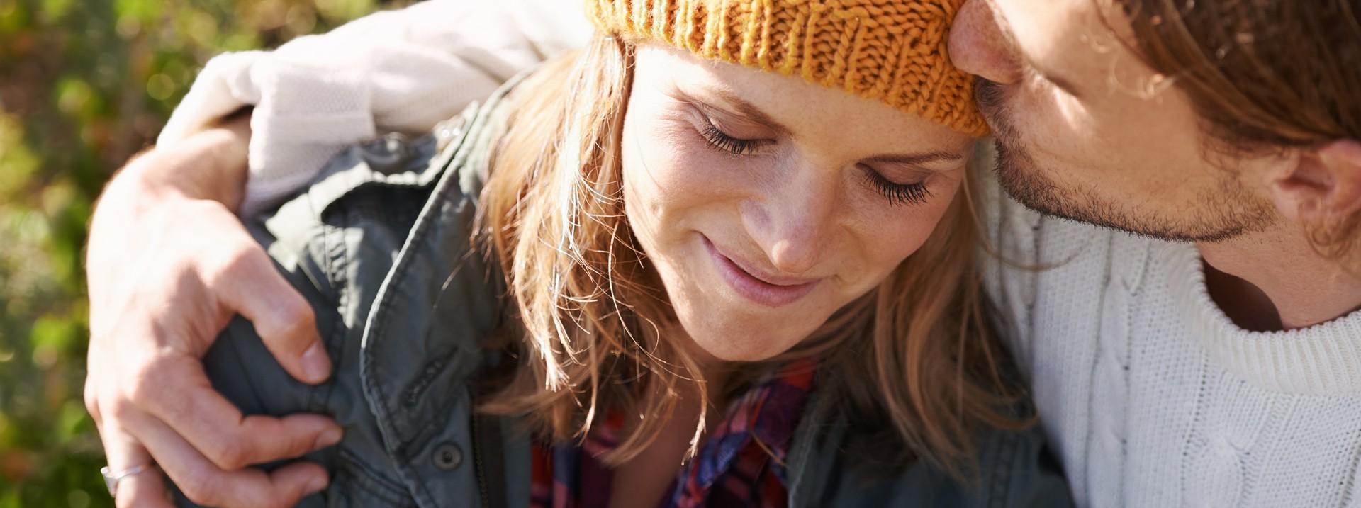 Mädchen liegt entspannt lächelnd auf der Wiese und stützt den Kopf in die Hände.