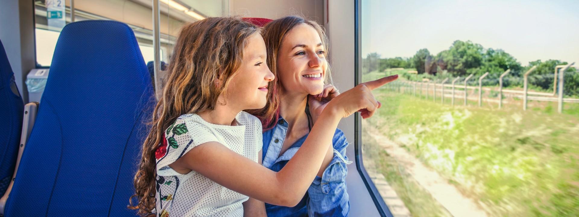 Mutter und Tochter sitzen zusammen im Zug und schauen lächelnd aus dem Fenster.