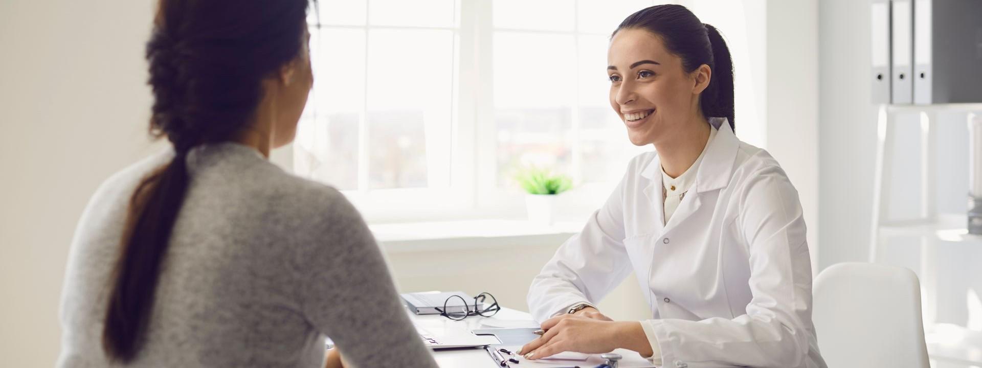 Eine etwa 35-jährige Ärztin sitzt in einem Behandlungszimmer und berät eine Frau.