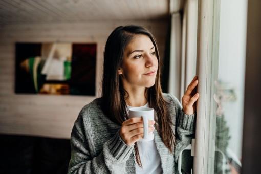 Eine etwa 25 jährige Frau steht an einem Fenster und schaut nach draußen. Sie hält eine Tasse in de Hand.
