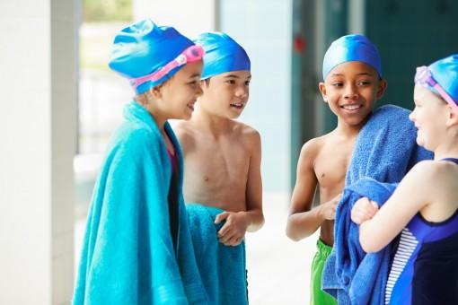 Vier etwa 10-jährige Kinder stehen im Schwimmbad in ihre Badetücher eingewickelt zusammen.