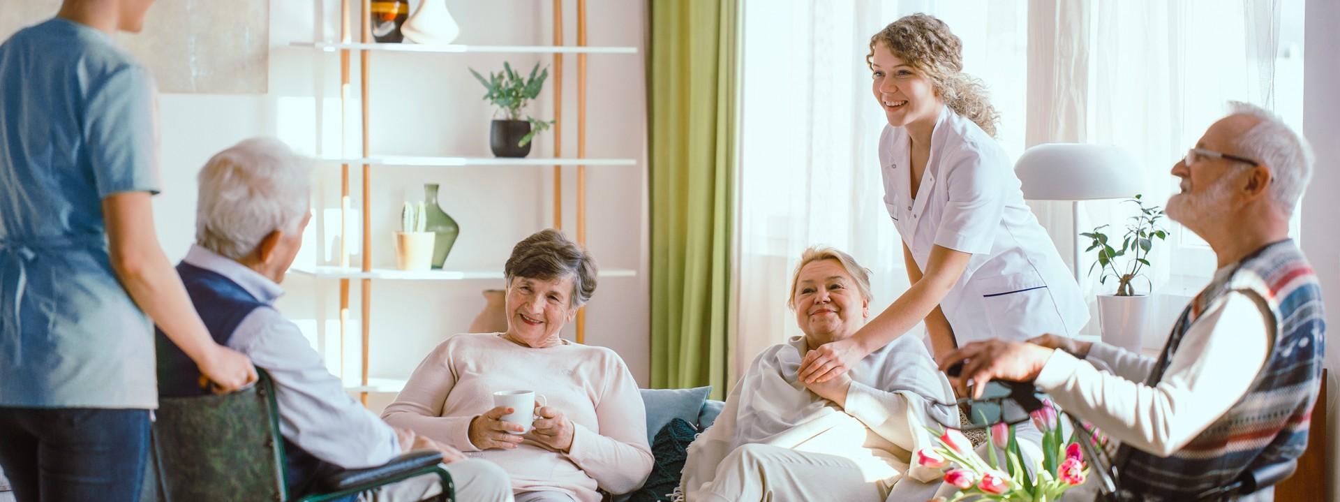 Vier Senioren und Seniorinnen sitzen zusammen. Neben ihnen stehen zwei Pflegerinnen.