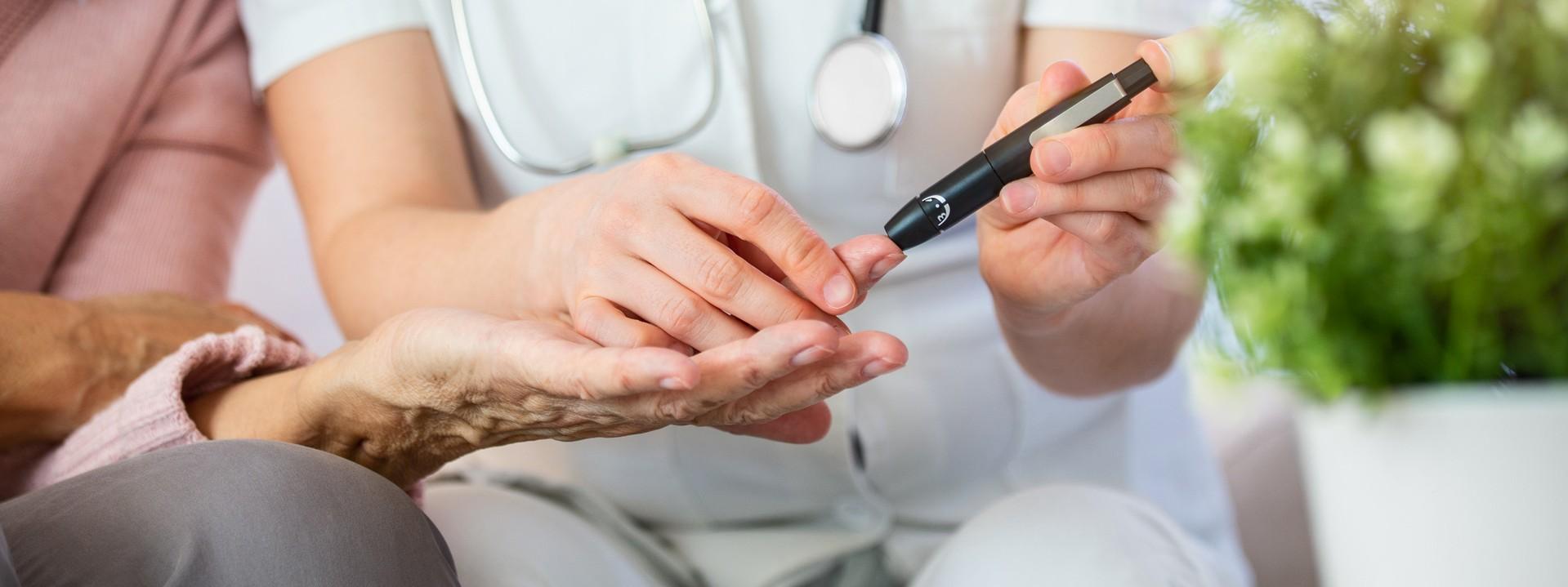 Eine Ärztin misst bei einer Seniorin den Blutzucker mit Hilfe eine Blutzuckermessgerätes am Finger.
