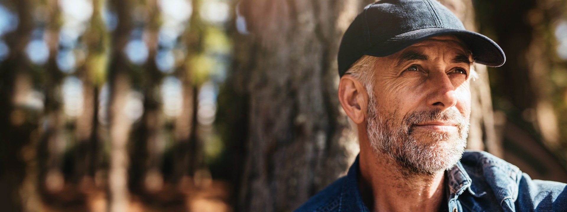 Ein Mann mit Mütze sitzt im Wald an einem Baum.