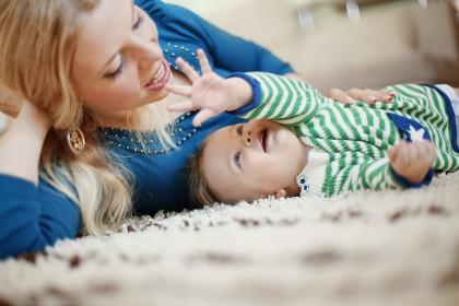 Frau mit kleinem Kind liegt auf Teppich.