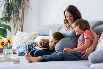 Schwangere Frau sitzt mit zwei Kindern auf dem Sofa