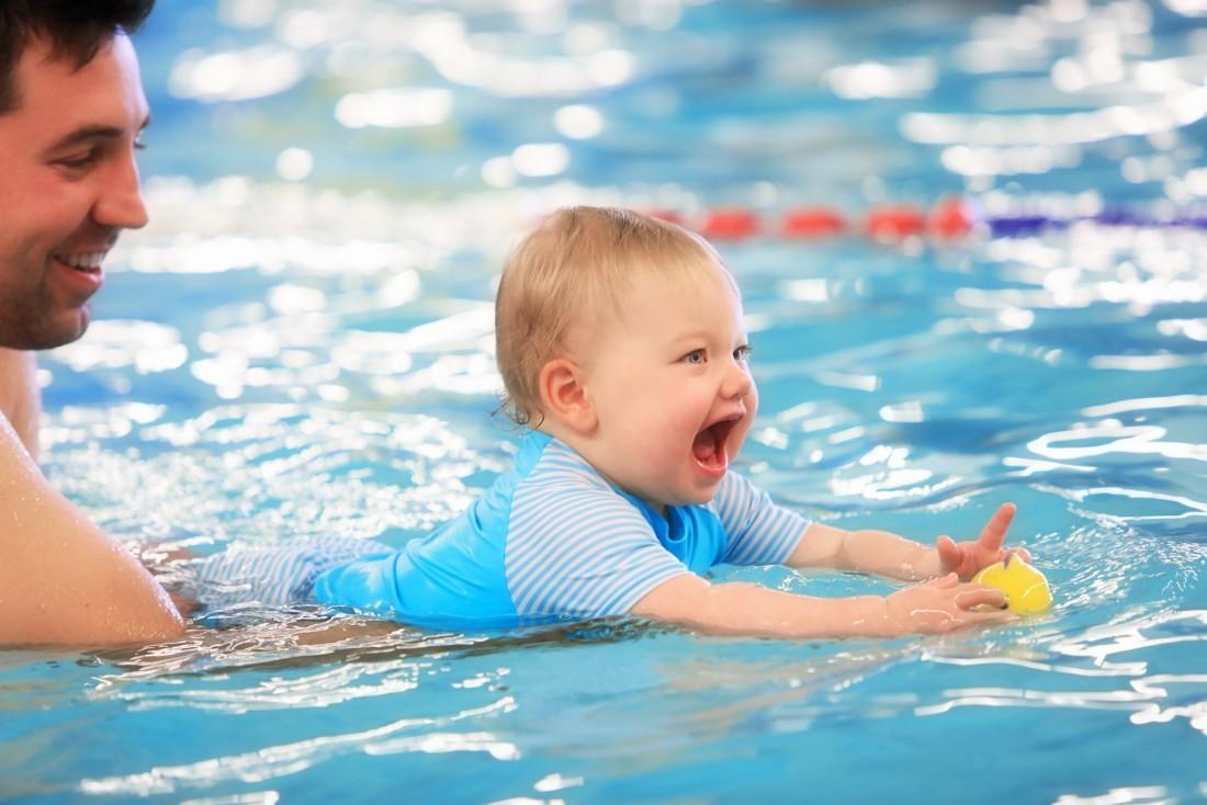 Vater mit Kind beim Babyschwimmen