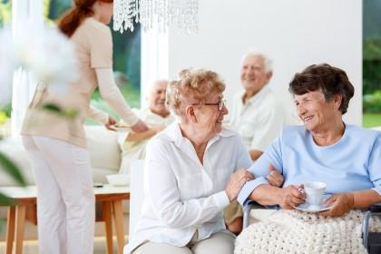 Vier Senioren sitzen zusammen, reden und lächeln sich an. Eine Pflegerin behandelt einen älteren Mann.