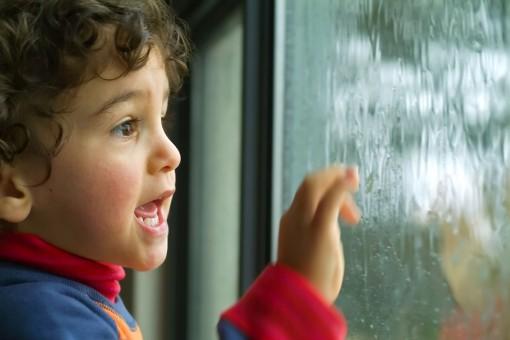 Ein etwa 2 jähriger Junge steht an einem Fenster und fasst an die Glasscheibe. Draußen regnet es.
