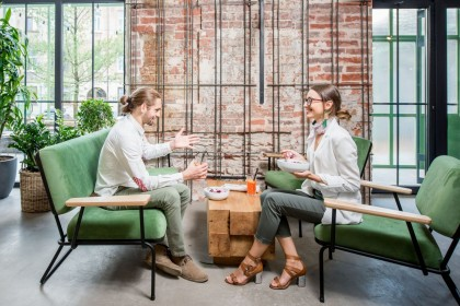 Zwei etwa 25 jährige Personen sitzen jeweils auf zwei Sofas in einem Café. Beide unterhalten sich und essen etwas aus einer Schale.