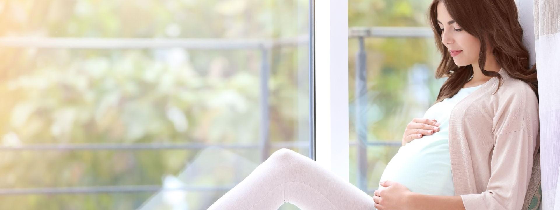 Eine etwa 25 jährige schwangere Frau sitzt seitlich an einem großem Fenster. Sie umfasst mit beiden Händen ihren Bauch.