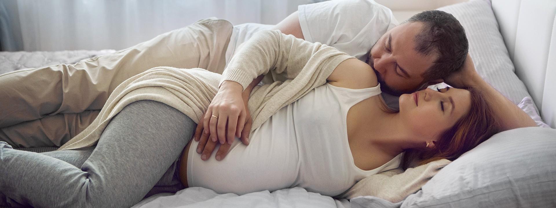 Mann sitzt lächelnd auf dem Sofa und seine schwangere Frau legt ihren Kopf in seinen Schoß während sie gemeinsam den Babybauch streicheln.