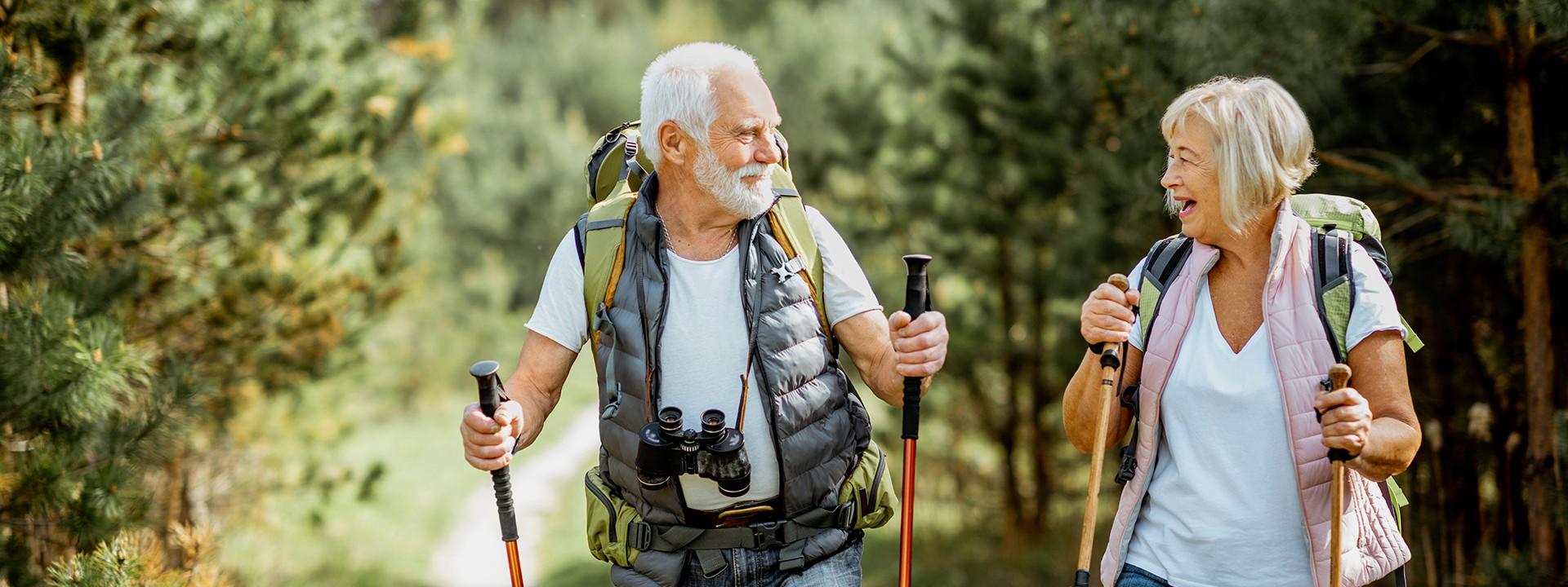 Senioren wandern fröhlich durch den Wald.