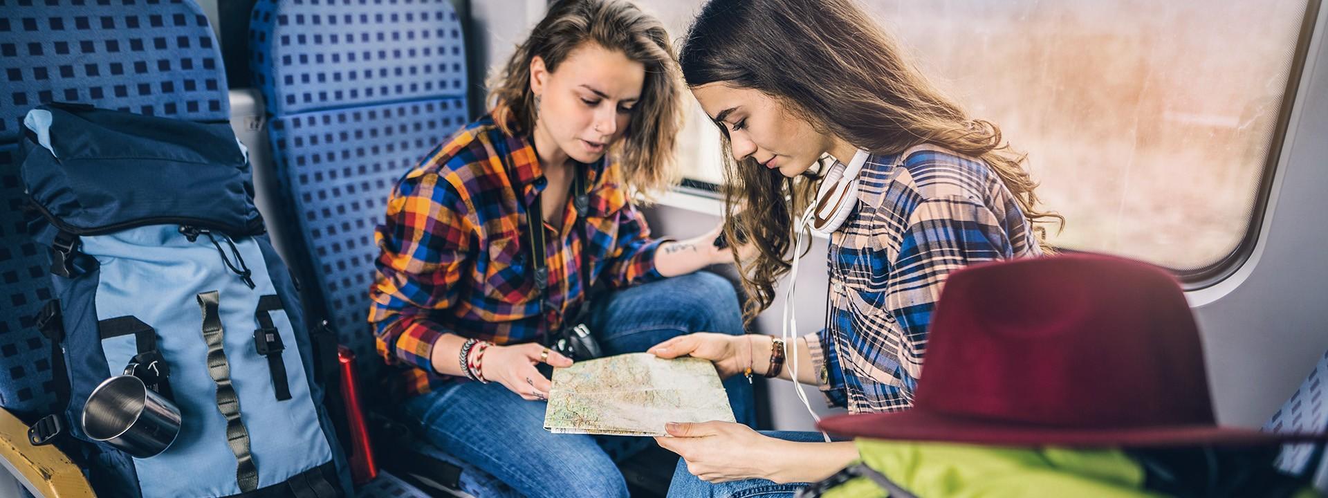 Zwei junge Frauen reisen mit viel Gepäck im Zug.