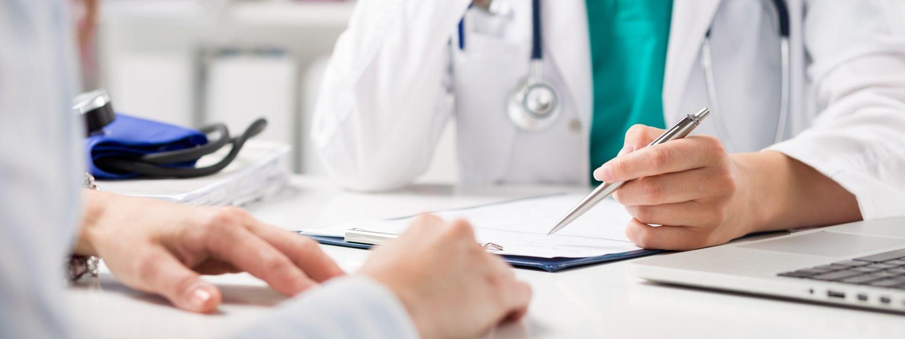 Eine Ärztin berät in einer Praxis eine Patientin. Dabei macht sie Notizen in den Unterlagen.