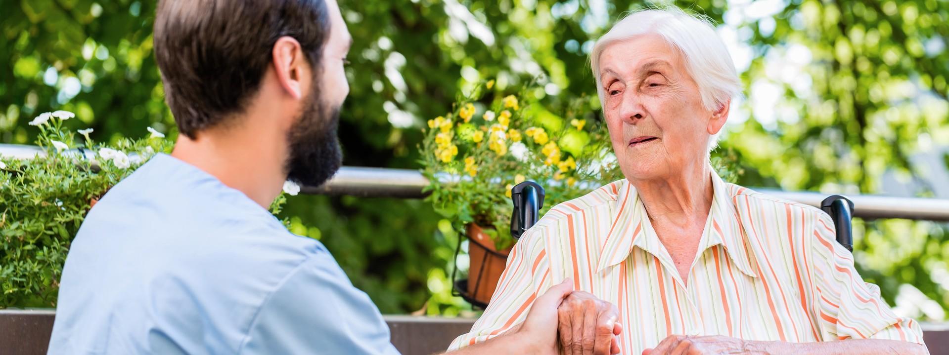 Pfleger mit Frau im Rollstuhl