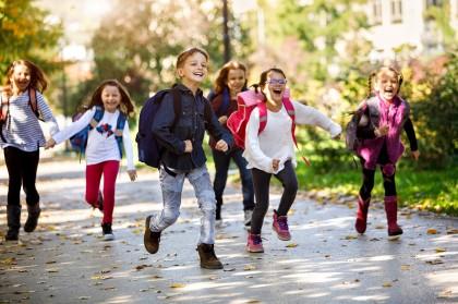 Erstklässler mit Schulranzen auf dem Weg zur Schule.