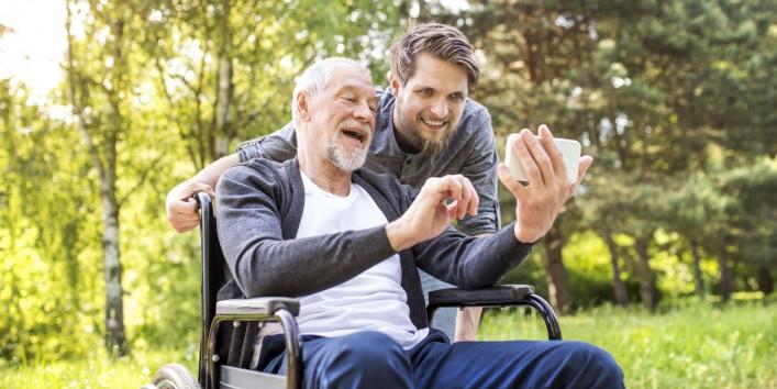 Ein etwa 60 jähriger Mann sitzt im Rollstuhl. Er hält ein Handy in der Hand und macht ein Selfie mit einem etwa 30 jährigen Mann, der hinter ihm steht. Beide befinden sich in der Natur und lachen ausgiebig.