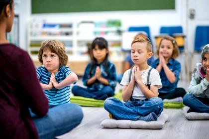 Kinder sitzen im Schneidersitz auf Matten und meditieren.