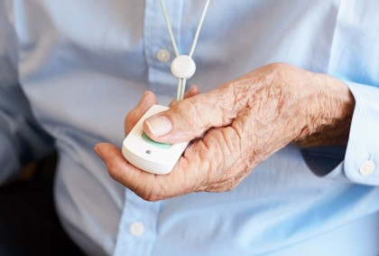 ein älterer Mann drückt den Hausnotrufknopf an seinem Funksender