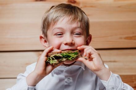 Ein etwa 5 jähriger Junge isst eine zusammen geklappte Schnitte mit Grünzeug. Dabei lächelt er und genießt.