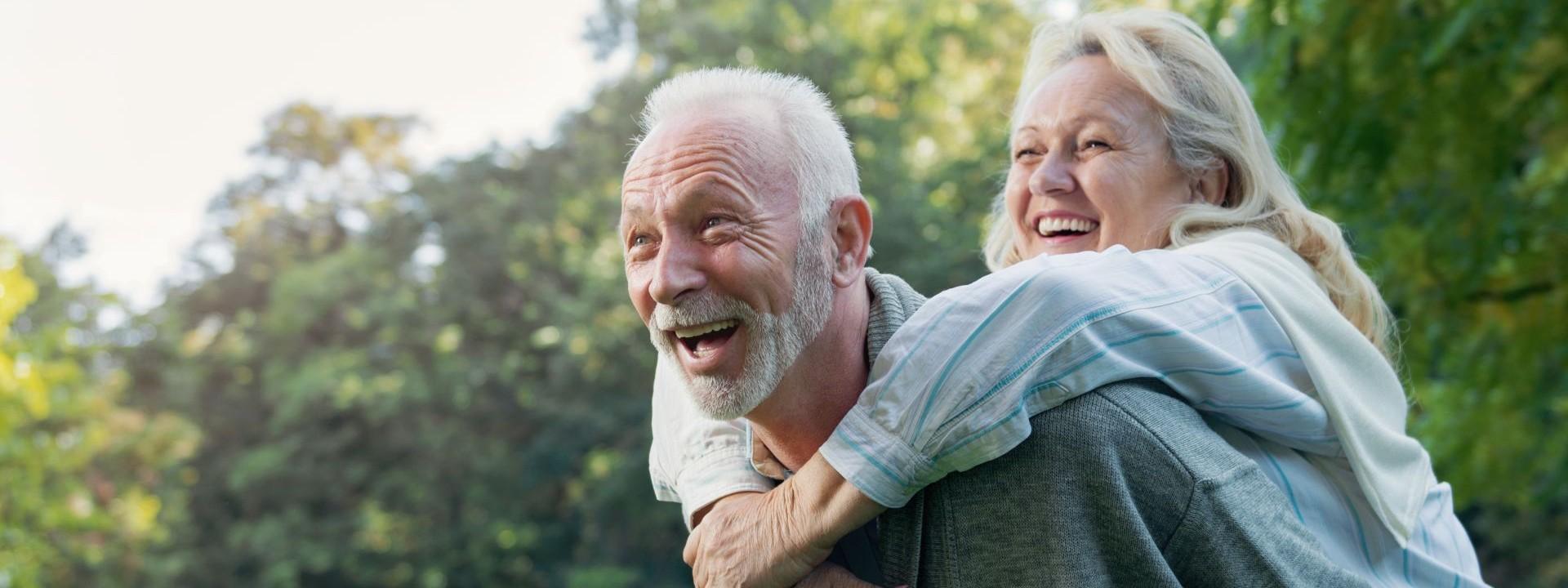 Ein Seniorenpaar hat gemeinsam in der Natur Spaß. Der Mann trägt die Frau auf dem Rücken. Beide lachen ausgiebig.
