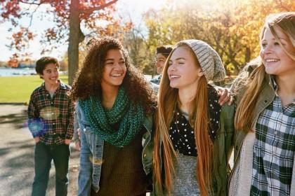 Eine Gruppe von 5 Teenagern fröhlich lächelnd in der Herbstsonne.