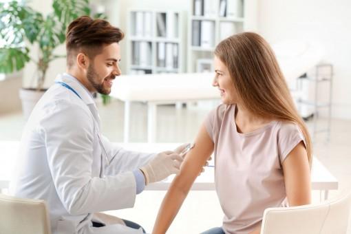 Eine etwa 35 jährige Frau wird von einem Arzt in den rechten Arm geimpft.
