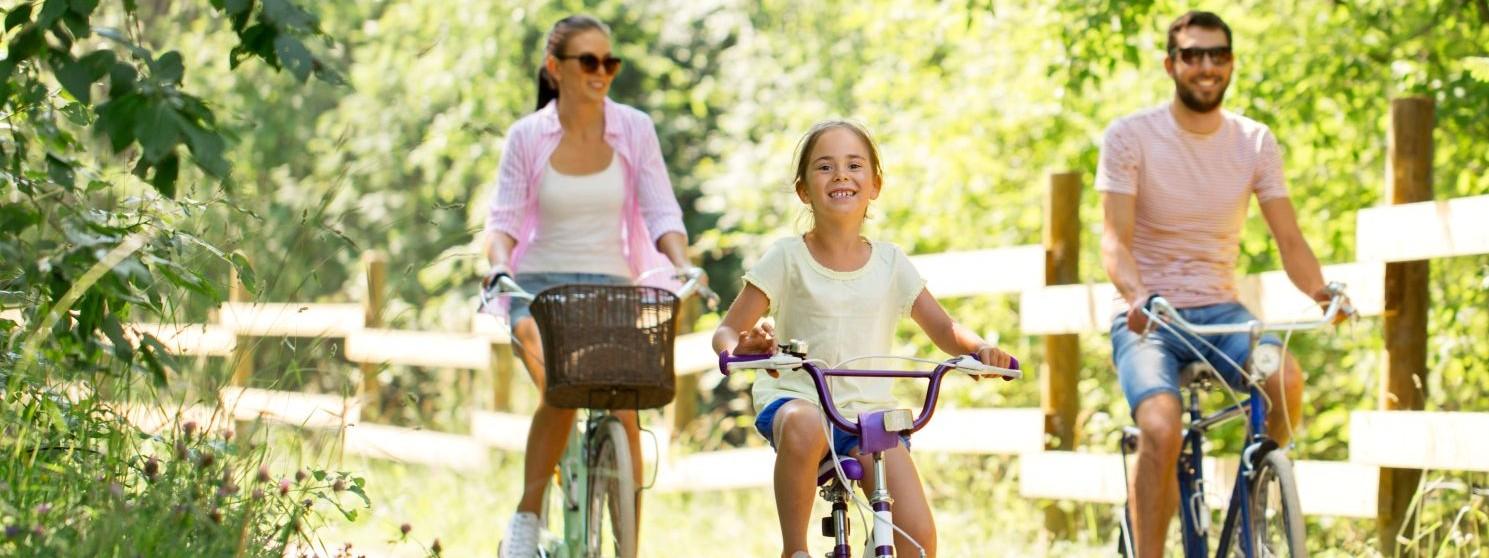 Eine junge Familie fährt mit ihren Fahrrädern durch die Natur.