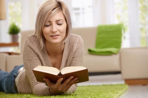 Eine etwa 30 jährige Frau liegt auf dem Boden im Wohnzimmer und liest in einem Buch.