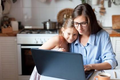 Eine etwa 30 jährige Mutter sitzt in der Küche am Tisch mit ihrer Tochter. Beide schauen auf einen Laptop, der vor ihnen steht.