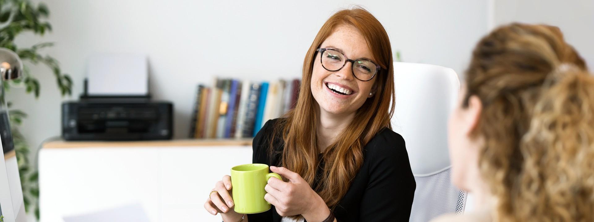 Eine circa 20-jährige Auszubildende macht am Platz kaffeepause mit ihrer Kollegin.
