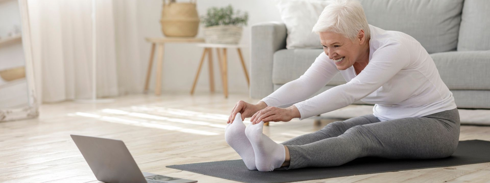 Eine Seniorin dehnt sich auf einer Sportmatte im Wohnzimmer. Dabei schaut sie auf einen Laptop der vor ihr steht.