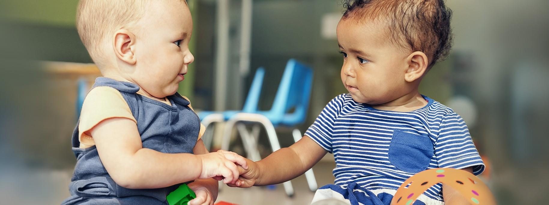Zwei Babies spielen zusammen mit bunten Bausteinen