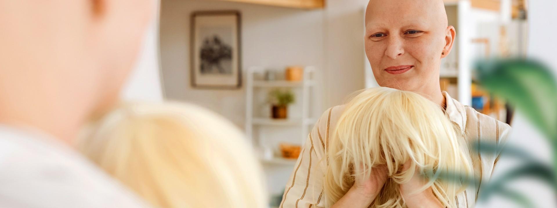Eine Frau mit Glatze schaut in einen Spiegel und hält eine blonde Perücke in der Hand.