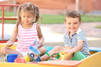 Zwei etwa 3 jährige Kinder sitzen in einem Sandkasten und spielen mit Schippen und dem Sand.