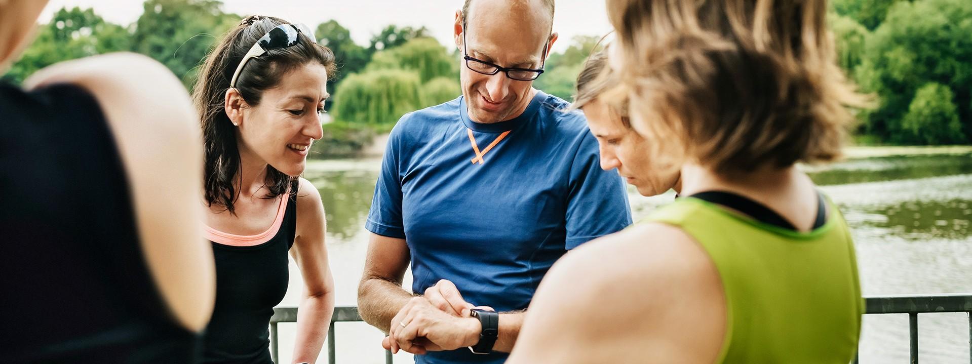 Läufer stehen in einer Gruppe zusammen und schauen auf Uhr