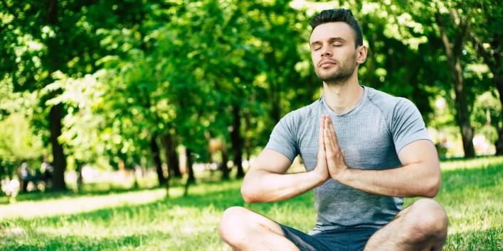 Ein etwa 25 jähriger Mann sitzt auf einer Yogamatte im Park. Er hat die Augen geschlossen und meditiert.