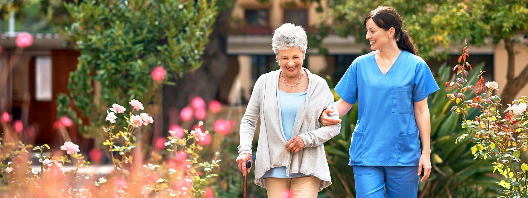 Pflegerin geht mit Seniorin spazieren