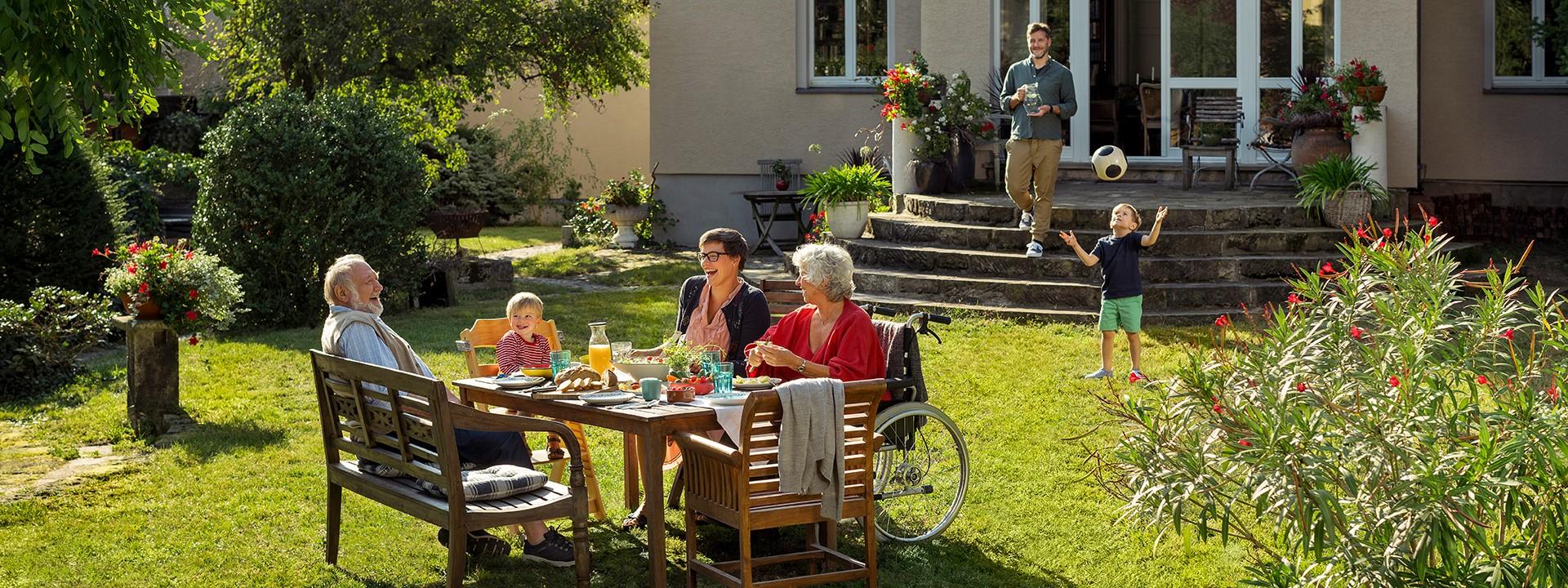 Großfamilie sitzt im Garten am Tisch
