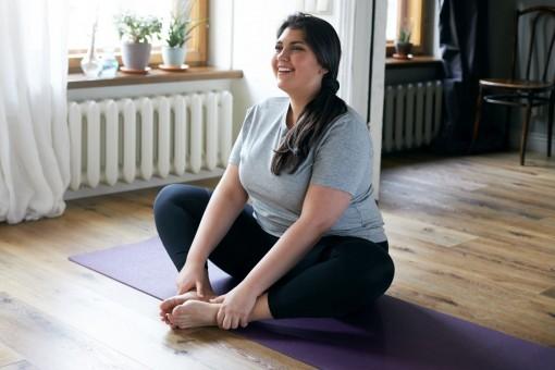 Eine etwa 25 jährige Frau sitzt im Schneidersitz auf einer Sportmatte in einem Zimmer. Dabei lächelt sie.