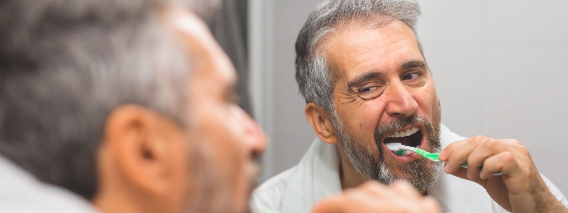 Ein etwa 45 jähriger Mann steht vor einem Spiegel im Bd und putzt sich intensiv mit einer Handzahnbürste die Zähne.